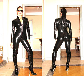 Catsuit - A woman wearing a black plastic zip front latex fetish catsuit and thigh-high boots.