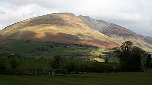Blencathra Shadows fall across the long grassy...