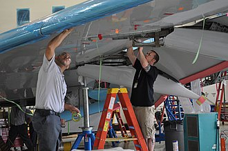 Aircraft maintenance - Technicians work on a Bombardier airplane in Dallas, Texas