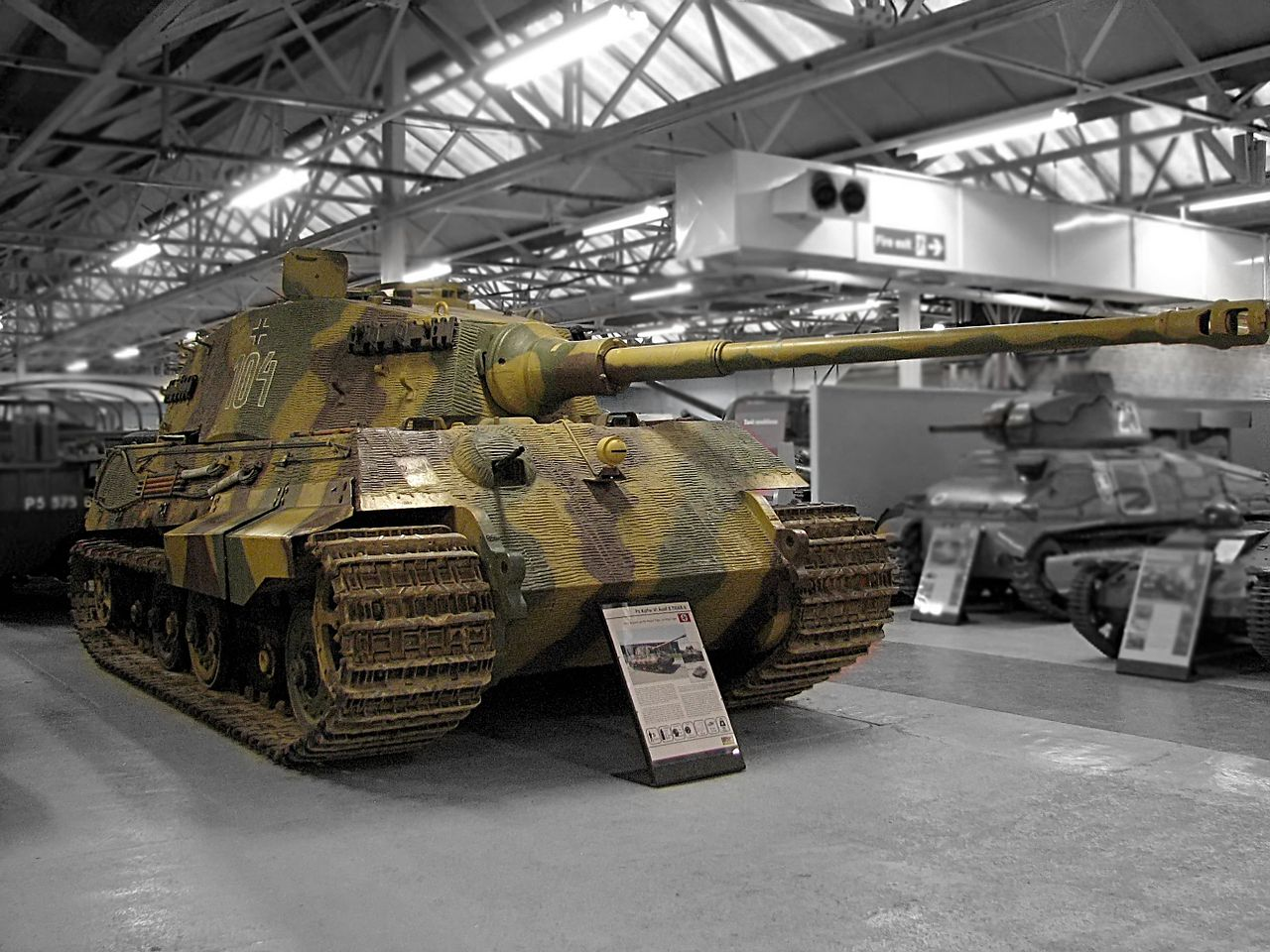 A large, turreted tank with dull yellow, green and brown wavy camouflage, on display inside Bovington museum. The tracks are wide, and the frontal armour is sloped. The long gun overhangs the bow by several meters.