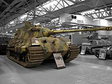 A large, turreted tank with dull yellow, green and brown wavy camouflage, on display inside a museum. The tracks are wide, and the frontal armour is sloped. The long gun overhangs the bow by several meters.