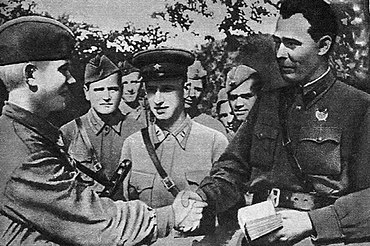 Brigade commissar Brezhnev (right) presents a Communist Party membership card to a soldier on the Eastern Front in 1943. Brezhnev 1942.jpg