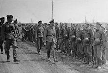 uma fotografia em preto e branco de um Heinrich Himmler de óculos em uniforme caminhando ao longo de uma fila de soldados em uniforme da Waffen-SS
