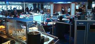 Bay Ferries - Main dining and lounge area, with two crew members about to open the gift shop in the background