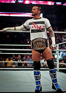 A man stands on a wrestling ring apron, a golden belt with the WWE insignia around his waist.
