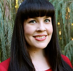 Caitlin Doughty in red evergreen background
