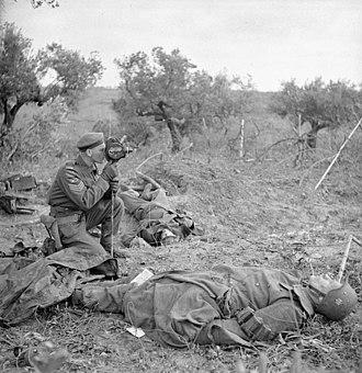 Canadian Army Film and Photo Unit - Sergeant George A. Game of the Canadian Army Film and Photo Unit operating his camera near San Leonardo di Ortona, Italy, December 10, 1943