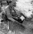 Canadian Press war correspondent Ross Munro typing a story in the battle area... Le correspondant de guerre de la Presse canadienne Ross Munro dactylographie un reportage sur un champ de bataille... (9199088933).jpg