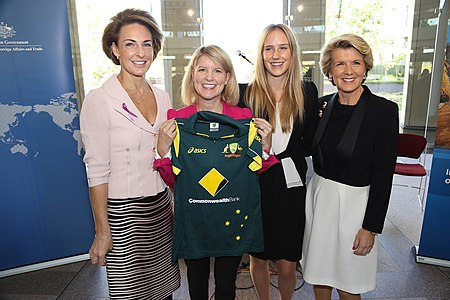 Perry poses for a photo next to the Minister for Foreign Affairs, Julie Bishop (right), after presenting an autographed Australian women's cricket team shirt to the Ambassador for Women & Girls, Natasha Stott Despoja (left).