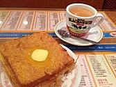 Pain doré à gauche, thé au lait à droite