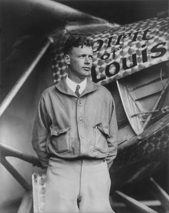 Knee high portrait of man in his twenties standing in front of an airplane labeled Spirit of St. Louis