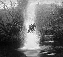 Two men crossing a rope bridge over water