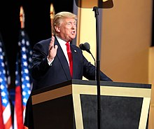 Trump standing behind a wooden, inverted-pyramid-shaped lectern with black paneling. He is speaking into a microphone, with an American flag hanging on a pole behind him. He is accepting the Republican nomination at the 2016 Republican National Convention in July 2016.