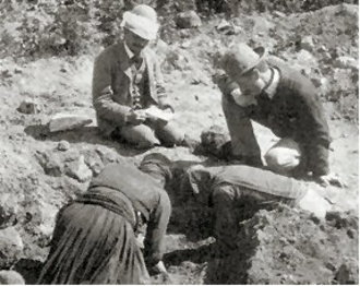 Duncan Mackenzie - Duncan Mackenzie is the man kneeling at the edge of the trench to the right. The figure at the left with the pith helmet is probably Arthur Evans. The woman in the centre remains unknown; she cannot be Evans' wife, as the latter had passed away well before the excavation of Knossos.