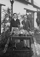 Gentleman and lady with golf clubs and three trophies