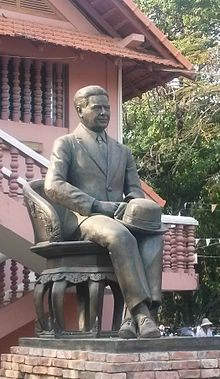 A cast-iron statue of a man in a suit with a hat in his lap, seated upon a chair also of cast iron; the wall and roof of a building is visible in the background.