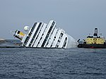Grounded and partially capsized Cruise ship Costa Concordia and the Ocean Crane Barge Meloria - 12 Feb. 2012.jpg