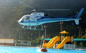 Wildfire suppression - A helicopter dips its bucket into a pool before dropping the water on a wildfire close to Naples, Italy.