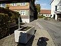 Hohenweiler Vorarlberg, Brunnen vor ehem Mesnerhaus, rechts Pfarrkirche.JPG