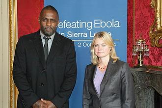 Justine Greening - Greening and actor Idris Elba at a Defeating Ebola virus conference (2014)