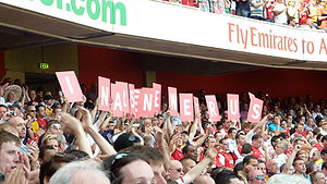 Arsenal supporters hold up cards that spell ou...