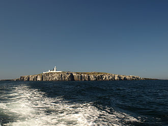 Farne Islands - Inner Farne and its lighthouse. There are white bird droppings on the cliff.