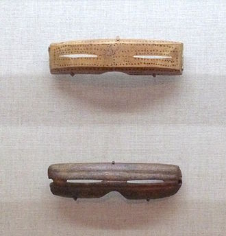 Snow goggles - Inuit snow goggles from Alaska. Made from carved wood, 1880-1890 (top) and Caribou antler 1000-1800 (bottom)