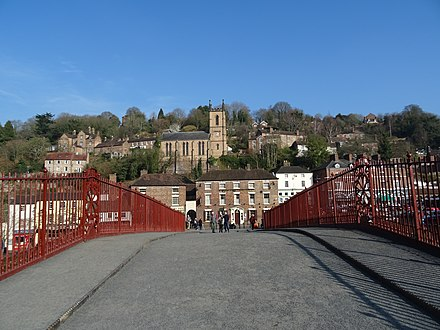 Pedestrians crossing the Iron Bridge with Ironbridge in the background in 2019, after the bridge had been conserved and the metalwork painted red. Iron Bridge roadway facing north, February 2019.jpg