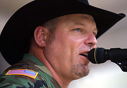 A man in a black cowboy hat and camouflage jacket singing into a microphone