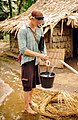Jake Ward collects water in a bucket from a village tap. (10705623996).jpg