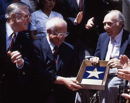 Johnny Grant, center, at producer Joe Pasternak's presentation ceremony in 1991. At left is Gene Kelly. Joe Pasternak Allan Warren.jpg