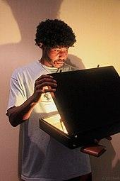 Un homme de race noire avec une coiffure afro vêtu comme le personnage de Jules Winnfield à la fin du film et ouvrant une mallette qui produit une forte lueur.