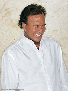 A man smiles and looks down. He is wearing a plain, white shirt.