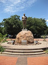 A bronze-colored, life-size statue of a prominent black man in a suit, his hands in front of his stomach. The statue is on top of a pedestal which is on top of a large brown rock, surrounded by smaller rocks. The statue has trees behind it, and it is in a small brick-paved square.
