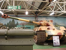 A frontal view of a large tank in a museum, painted pale yellow with some green and rust-brown blotches. Its curved-faced turret is turned to the left and the long gun overhangs the side by several meters.
