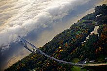 Aerial view of a bridge approaching a fog-covered river