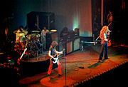 A colour photograph of the four members of Led Zeppelin performing onstage, with some other figures visible in the background. The band members shown are, from left to right, the bassist, drummer, guitarist, and lead singer. Large guitar speaker stacks are behind the band members.