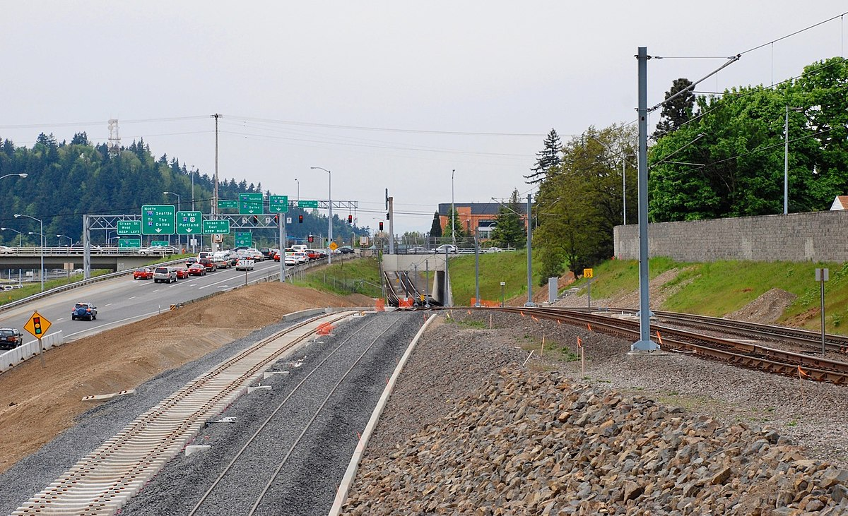 Photograph of the MAX Green Line under construction shows the underpass under Glisan Street and two new track lines—one completed. They are next to the Blue Line tracks at right in this photo. The exit ramp from northbound I-205 to Glisan Street is at the left.