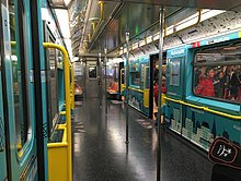 The interior of a R62A subway car used on the 42nd Street Shuttle, which was retrofitted to increase capacity. Almost all of the seats have been removed and replaced with a wallpaper with art on it.