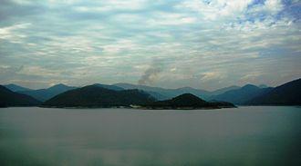 Doi Saket District - Mae Kuang Dam (เขื่อนแม่กวงอุดมธารา) in Doi Saket with the Khun Tan Range in the background and a seasonal wildfire