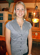 A blonde woman in casual clothes smilies into the camera. She wears a top with a narrow pattern of black and white strips and stands in a room with traditional Bavarian interior.