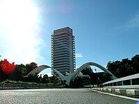 Fotografie ukazuje na malajské budově parlamentu společně s 2 bílými oblouky v diagonální pozici před budovou.