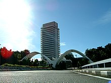 A photo showing the Malaysian Parliament building along with two white arches in diagonal position front of the building.