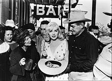 "Monroe in The Misfits, holding a wide-brimmed hat filled with dollar bills and standing next to Clark Gable and Thelma Ritter. Behind them is a sign spelling ""BAR"" and a crowd of people."