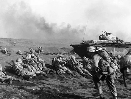 U.S. Marines of the Second Battalion, Twenty-Seventh Regiment, wait to move inland on Iwo Jima, soon after going ashore on 19 February 1945. An LVT(A)-5 amphibious tractor is in the background. Red Beach One. Marines with LVT(A)-5 in Iwo Jima 1945.jpg