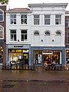 foto van Markt 12, een pand met lijstgevel met in de eerste verdieping geprofileerde boogvensters en consoles onder de kroonlijst