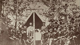 9th Regiment Massachusetts Volunteer Infantry - Men of the 9th Regiment and their chaplain pause before celebrating mass at Camp Cass, Virginia, 1861.