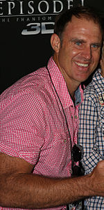 A man wearing a pink shirt looks across his shoulders.