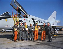 The astronauts pose in front of a delta-winged light blue-gray jet aircraft, holding their flight helmets under their arms. The three Navy aviators wear orange  flight suits; the Air Force and Marine ones are green.