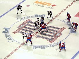 Several ice hockey players in red uniforms line up around the near half of a large circle on the ice, opposed on the other side by several in white uniforms. A player from each team stands at the centre of the circle, joined by a referee wearing a vertically striped black and white uniform.